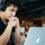 Photo of a young man with headphones on working on a laptop