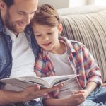 photo of a dad reading with his son on the couch
